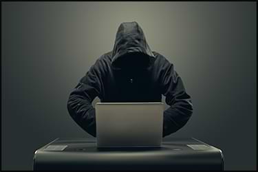 האקר עם פנים מוסתרות מול מחשב נייד