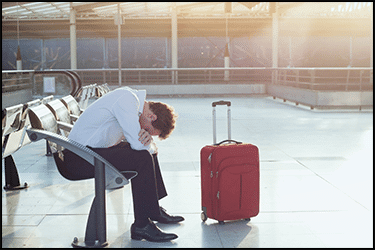 בן אדם עצוב/עייף עם מזוודה בשדה התעופה