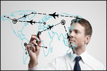 איש עסקים צעיר מצייר נתיבי מטוס על מפת העולם על חלון זכוכית