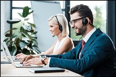 נותן שירות שמח עם אוזניות מקליד במחשב נייד ליד עמיתו הבלונדינית