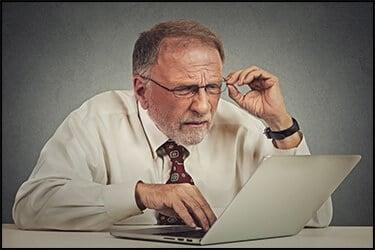 אדם מבוגר עם משקפיים יושב מבולבל מול מחשב נייד