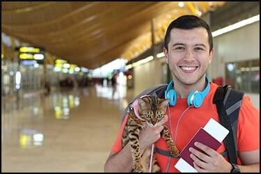 אדם שמח עם חולצה אדומה ואוזניות כחולות עומד עם תיק על הגב שלו בשדה התעופה. הוא מחזיק ביד אחת חתול וביד השניה דרכון וכרטיס טיסה