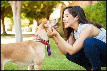 בחורה שמחה עם כלב בצבע בז'