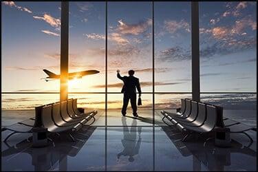 איש עסקים בשדה התעופה מסתכל מחוץ לחלון גדול ורואה מטוס ממריא בשקיעה