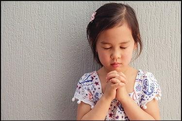 ילדה קטנה אסייתית שמתפללת בעיניים עצומות