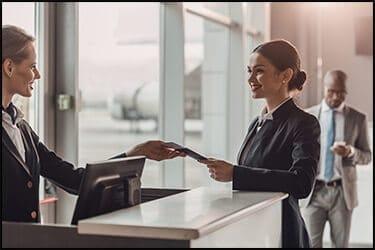 אשת עסקים צעירה מחייכת שנותנת דרכון וכרטיס טיסה לצוות בדלפק הצ'ק אין שדה תעופה