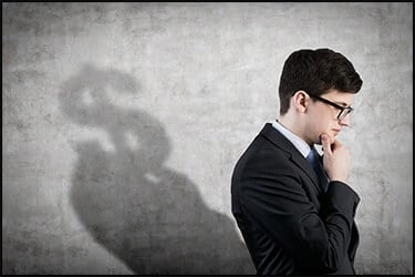 Businessman thinking about the VIP service cost. In his shadow you see a big dollar sign