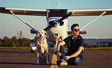 הטסת כלב - כלב והבעלים שלו יושבים ליד מטוס