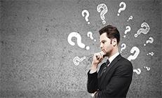 איש עסקים בחליפה שחורה שחושב. באוויר מצוירים סימני שאלה לבנים.