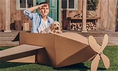 Boy saluting with puppy in cardboard airplane