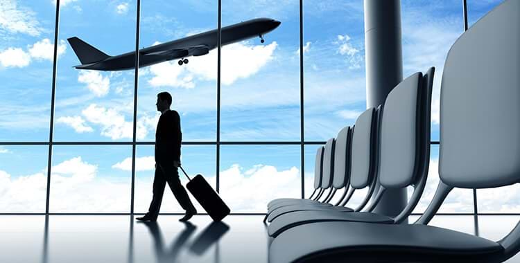 A businessman walks with his suitcase at the airport. You see a plane taking off through the windows