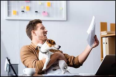 איש שמח מחזיק כלב ומסתכל על מסמך שקיבל